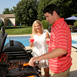 Man and woman grilling beside a pool
