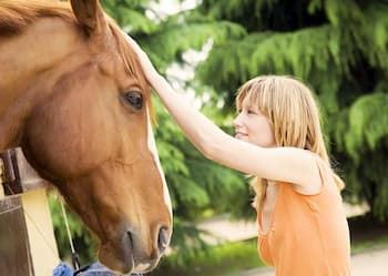 Young lady petting horse.