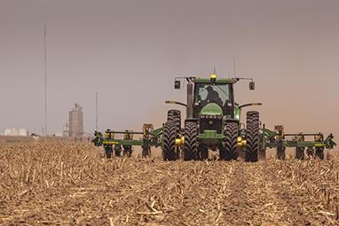 A tractor plants corn in a field