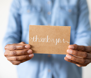 stock photo of hands holding thank you card